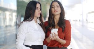 Two pretty stylish women reading an sms. Or text message on a mobile phone with serious expressions as they stand together in an urban street stock video footage