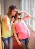 Two pretty teenage girls  having fun in sunroom Royalty Free Stock Image