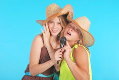 Two pretty thirteen year old girls wearing a big floppy straw sun hat Royalty Free Stock Image