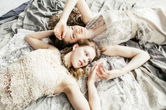 Two pretty twin sister blond curly hairstyle girl in luxury house interior together, rich young people concept. Close up Royalty Free Stock Images