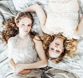Two pretty twin sister blond curly hairstyle girl in luxury house interior together, rich young people concept. Close up Royalty Free Stock Photography