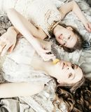 Two pretty twin sister blond curly hairstyle girl in luxury hous royalty free stock photo