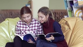 Two pretty university girls sitting in library and looking into books stock video