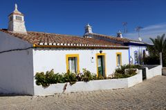 Pretty white houses in Cacela Velha, Algarve, Portugal. Two pretty white stucco houses with red tile roofs and chimneys in small fishing village of Cacela Velha royalty free stock photos