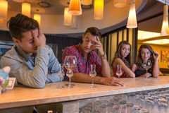 Two pretty woman at the bar, looking seductively, the handsome men Royalty Free Stock Image
