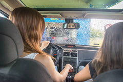 Two pretty woman in the car during the car wash Stock Photos