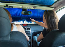 Two pretty woman in the car during the car wash.  Two pretty women in the car during the car wash Stock Photography