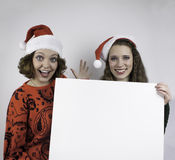 Two pretty woman holding sign Royalty Free Stock Image