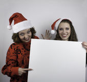 Two pretty woman holding sign Stock Photos