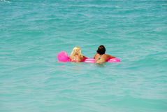 Two pretty women. On top of an air mattress, in the sea of caraeibas stock images