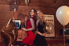 Two pretty women in cocktail dresses posing with balloons at birthday party in stylish cafe.  royalty free stock photo