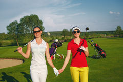 Two pretty women golfers walking at golf course Stock Images