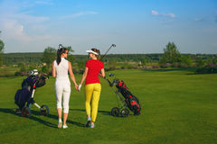 Two pretty women golfers walking at golf course Royalty Free Stock Image