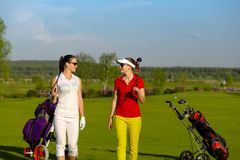 Two pretty women golfers walking at golf course royalty free stock photo