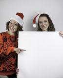 Two pretty women holding sign for copy space Stock Photos