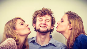 Two pretty women kissing handsome man. Love triangle royalty free stock photography