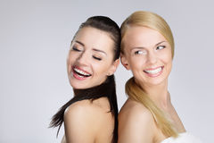 Two pretty women leaning on each other back laughing. Close up portrait of two pretty women leaning on each other back laughing Stock Photography