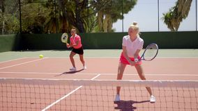 Two pretty women playing a game of tennis doubles. Two attractive shapely young women playing a game of tennis doubles standing ready to receive service stock footage