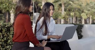 Two pretty women sharing a laptop outdoors stock footage