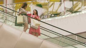 Two pretty women standing on the down escalator of a shopping mall stock video footage