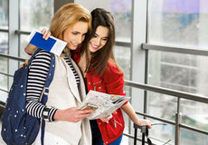 Two pretty women standing in the terminal with a suitcase, a backpack and a look at the map. Stock Photography