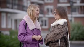 Two pretty women are standing in yard of living buildings in a city in autumn and chatting, one friends is speaking stock footage