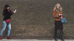 Two pretty women are walking on the enbankment of icy river and feeding pigeons. Two women, blonde and brunette, are walking on the enbankment of icy river and stock video