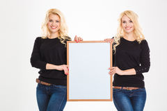 Two pretty young blonde sisters twins holding blank board. Over white background Royalty Free Stock Photos