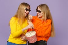 Two pretty young blonde twins sisters girls in 3d imax glasses watching movie film, holding popcorn  on pastel stock photo