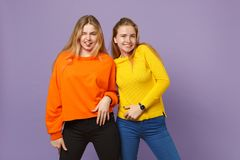 Two pretty young blonde twins sisters girls in vivid colorful clothes looking camera showing tongue isolated on pastel