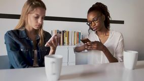 Two pretty young business women using their mobile phones in the office. Video of two pretty young business women using their mobile phones in the office stock footage