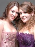 Two Pretty Young Females. Two females pose in satin formal dress attire.  Portrait shows fancy bodice on both young women.  Hair is curled and the are standing Stock Images
