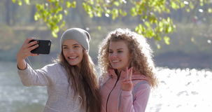 Two Pretty Young Girl Taking Selfie Photo On Cell Smart Phone Near Tree Outdoor Sunrise, Morning Autumn Park. Natural Sun Lights Slow Motion 60 stock video