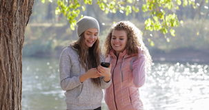 Two Pretty Young Girl Using Cell Smart Phone Near Tree Outdoor Sunrise, Morning Autumn Park. Natural Sun Lights Slow Motion 60 stock video footage