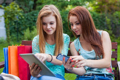 Two pretty young girls looking for new sales using tablet. Royalty Free Stock Images