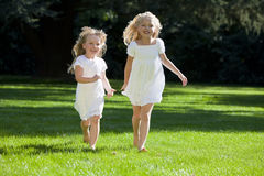 Two Pretty Young Girls Running In A Green Park royalty free stock photos