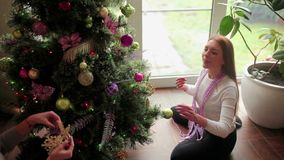 Sisters sit on floor and decorate Christmas tree. Two pretty young girls sitting on the floor and laughing. The beautiful brunette talking with her sister and stock footage