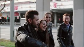 Two pretty young girls and two handsome men laugh happyily while walking in the city. Steadicam shot, slow mo. Two pretty young girls and two handsome young men stock footage