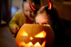 Two pretty young sisters in halloween costumes carving a pumpkin together Royalty Free Stock Photos