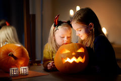 Two pretty young sisters in halloween costumes carving a pumpkin together Stock Photos