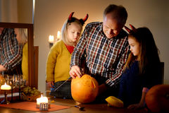 Two pretty young sisters in halloween costumes and their grandpa carving a pumpkin together Royalty Free Stock Photo