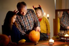 Two pretty young sisters in halloween costumes and their grandpa carving a pumpkin together Royalty Free Stock Photos