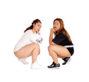 Two pretty young woman crouching. Two lovely woman, Caucasian and East Indian, crouching on the floor Stock Images