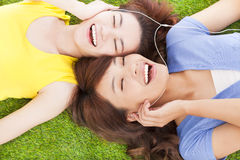 Two pretty young woman lying on grassland and listening music Stock Image