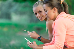Two Pretty young woman in sporty outfit using a smartphone Stock Photography