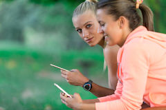 Two Pretty young woman in sporty outfit using a smartphone Stock Images