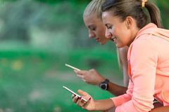 Two Pretty young woman in sporty outfit using a smartphone Royalty Free Stock Photography