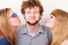 Two pretty young women kissing handsome man. Two pretty young women in glasses kissing handsome man. Love triangle royalty free stock image