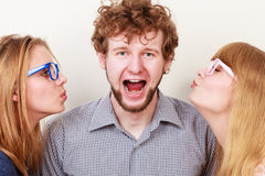 Two pretty young women kissing handsome man. Two pretty young women in glasses kissing handsome man. Love triangle royalty free stock photos