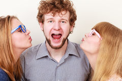 Two pretty young women kissing handsome man. Two pretty young women in glasses kissing handsome man. Love triangle stock photography